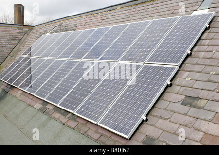 Solar PV (photovoltaic) panels on a school roof for electricity production. - Stock Photo