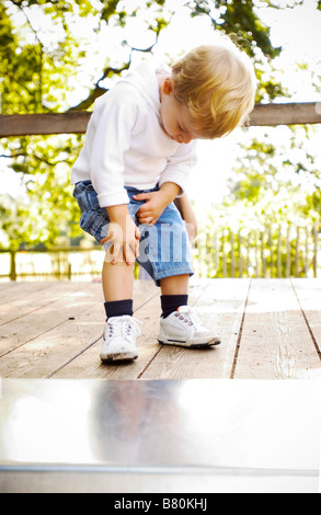 little boy at playground looking at his knee - Stock Photo