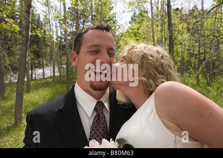 bride kissing the happy groom outdoors, wedding ceremony - Stock Photo