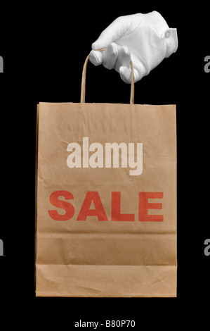 Hand in a white glove holding a brown recycled paper shopping bag with the word SALE written on it isolated on black - Stock Photo