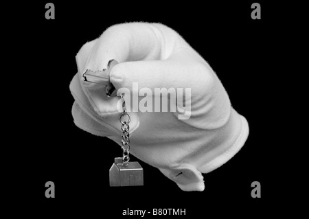 A hand in a white glove holding the key to a new house isolated on black - Stock Photo