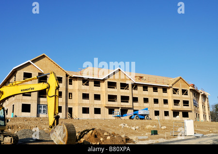 Apartment building construction site with the exterior wood frame and Komatsu excavator heavy equipment on site - Stock Photo