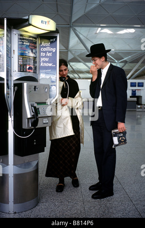 Oct 7, 2003 - Orthodox Jews calling home from a public BT payphone inside Stansted airport's departure hall. - Stock Photo