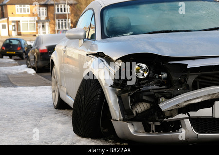 Stock photo of a crashed car showing the damage to its front wing The car was parked on the roadside in snowy weather - Stock Photo