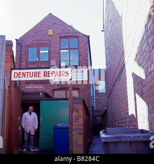 A backstreet denture repair workshop in Leicester with an employee taking a cigarette break - Stock Photo