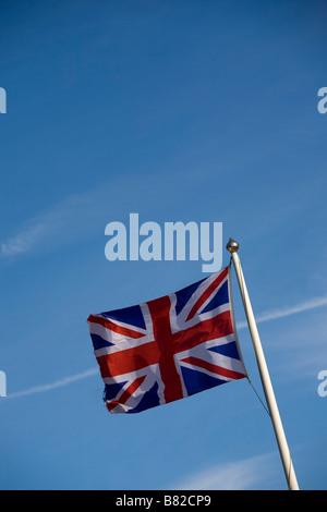 Union Jack flag flying on flagpole against blue sky - Stock Photo