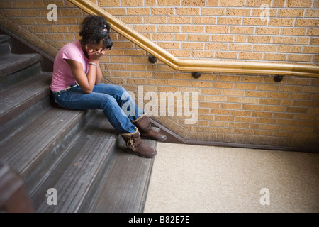 teenage african american girl crying on staircase at school, sitting on step - Stock Photo