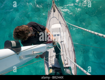 A sailor looks out from halfway up the mast on a cruising sailboat in the Caribbean - Stock Photo