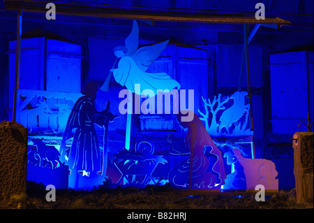 BLUE ILLUMINATED CHRISTMAS NATIVITY SCENE WITH CRIB IN GARDEN DURING ADVENT TIME AT NIGHT ALSACE FRANCE - Stock Photo