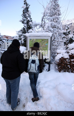 Two young tourists looking at a map in Chamonix Mont Blanc, France - Stock Photo