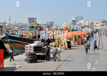 Dubai Creek and dhows with goods and merchandise stacked on the quayside - Stock Photo