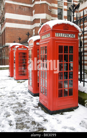 Four red telephone boxes in a row in snow - Stock Photo
