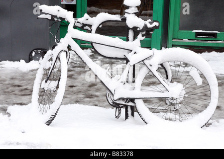 A parked bicycle decoratively covered in a fresh layer of snow - Stock Photo