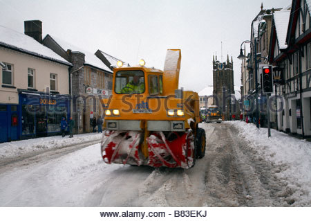 Snow clearing vehicle with heavy snow in town centre Fore Street Okehampton Devon England UK - Stock Photo