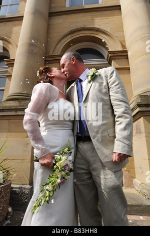 Newly wed couple kissing outside a registry office, North Yorkshire Model Released - Stock Photo