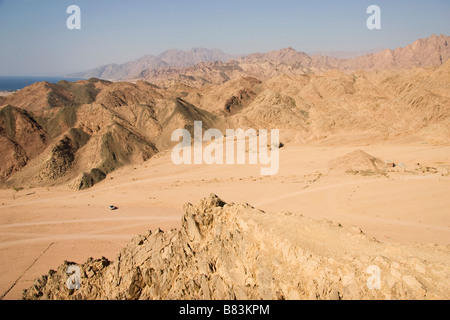 View South towards Laguna Bay from a hill in the desert above the Sinai resort of Dahab in Egypt - Stock Photo