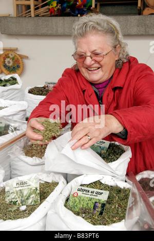 Herbal tea (caj) lady serving a customer on her stall in Plecnik's Market in Pogacarjev trg, in Ljubljana, Slovenia - Stock Photo