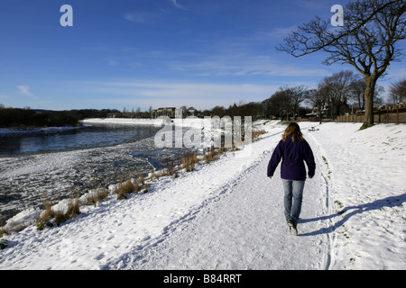 Walker on path beside frozen River Dee in the city of Aberdeen, Scotland, UK, with huge chunks of ice and snow during - Stock Photo