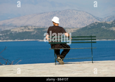 Young man in a white sun hat sitting on a bench resting at the hill of Kouloura, Corfu, Greece, Europe, EU - Stock Photo