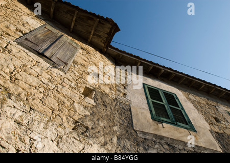 Brick house wall with two windows closed shutters over the sky in Omodhos village, Troodos mountains, South Cyprus - Stock Photo