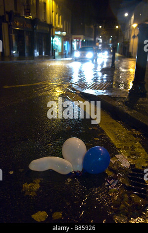 Party baloons lie abandoned in a gutter on a wet and windy night at Carmarthen Carmarthenshire Wales United Kingdom - Stock Photo