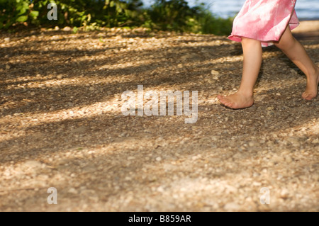 detail of little girl walking barefoot through forest - Stock Photo