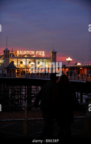 A couple stand standing with their arms around each other in front of Brighton Pier at night. Picture Jim Holden.
