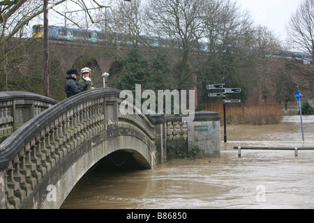 pedestrians on a footbridge watching flood water rise when the river chelmer flooded its banks in chelmsford - Stock Photo