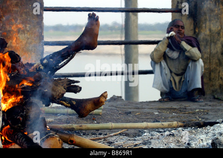 A body is burning on a funeral pyre on a ghat along the Ganges river in the holy city of Varanasi in India - Stock Photo