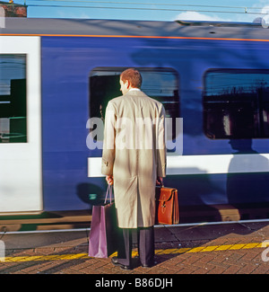 A  commuter and moving train in motion waiting with shopping bag on the platform at Stratford Station in East End - Stock Photo