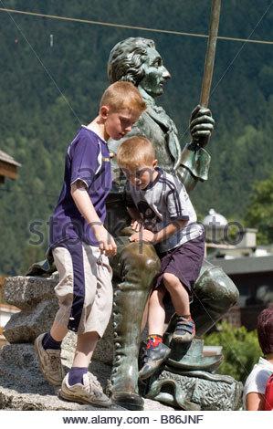 Chamonix: children playing around Paccard statue - Stock Photo