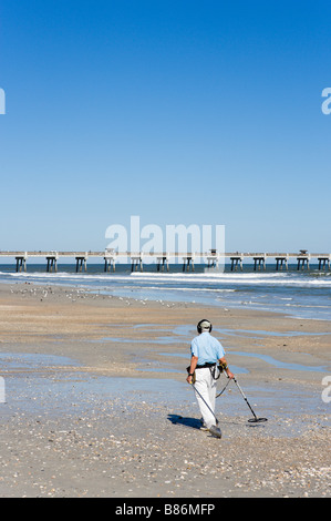 Elderly man beach combing with a metal detector in front of the pier, Jacksonville Beach, Florida, USA - Stock Photo