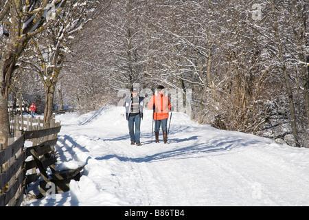 Pinzgau Region Austria EU January A woman and a man walking along a Winterwanderweg a cleared walking path - Stock Photo
