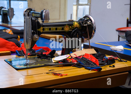 Old-school sewing machine at Tibetan school for women. They learn the craft of sewing. - Stock Photo