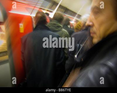 Commuters boarding a bust tube train IN LONDON - Stock Photo