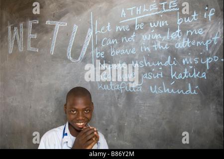 Girl with an intellectual disability writing on a blackboard,  Mabogini, Kilimanjaro Region,  Tanzania - Stock Photo
