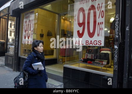 Shoppers pass a store selling discounted womens handbags in the Soho neighborhood of New York - Stock Photo
