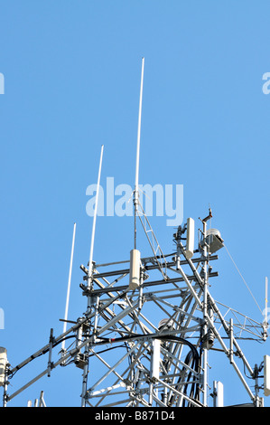 Top part of a cell phone tower against clear blue sky showing antennas for transmitting cellular mobile phone signals - Stock Photo