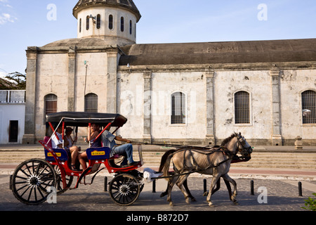 Tourists riding horse drawn carriage in front of the Iglesia de Guadalupe, Granada, Nicaragua. - Stock Photo