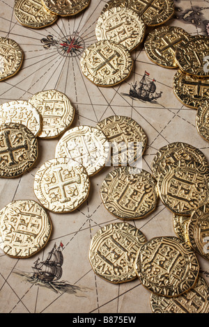 Gold coins doubloons on very old map - Stock Photo