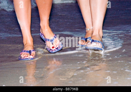 Two pairs of feet walk in shallow water wearing flip flops Model released - Stock Photo