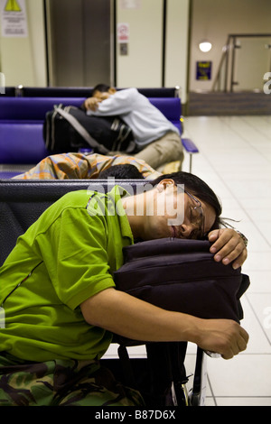 Young men sleep on chairs in the departure lounge of Bahrain international airport, while waiting for a flight. - Stock Photo