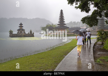 Tourists visit Ulun Danu Temple on a rainy day, Bali, Indonesia - Stock Photo