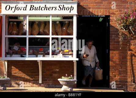 A woman carrying a shopping basket leaves a traditional local butchers shop in Orford. Woodbridge Suffolk England - Stock Photo
