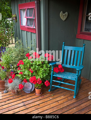 Vashon Island, WA: Colorful deck with potted flowers and blue rocker in the village of Ellisport - Stock Photo