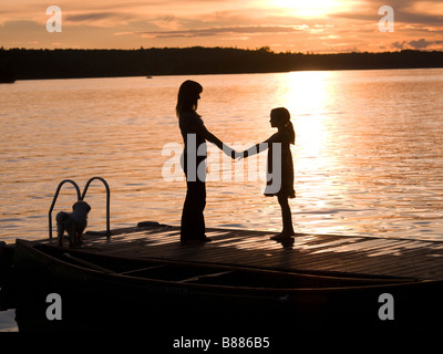 Silhouette of mother and daughter on a dock, Lake of the Woods, Ontario, Canada - Stock Photo