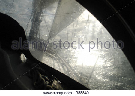 View through a sprayhood of a sailing yacht beating to windward on port tack - Stock Photo