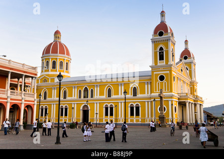 School children playing in the Parque Central in front of Our Lady of the Assumption Cathedral or Granada Cathedral - Stock Photo