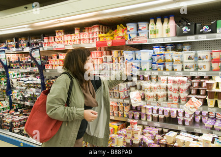 Conscience shopper comparing prices and ingredients in a supermarket dairy fridge Model Release Available - Stock Photo