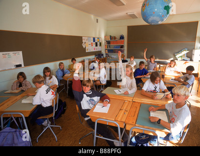 Students in 5th grade Swedish classroom sitting at desks with raised hands during question and answer session - Stock Photo